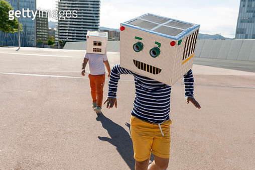 Carefree boy wearing robot mask dancing while friend walking on street in city - gettyimageskorea