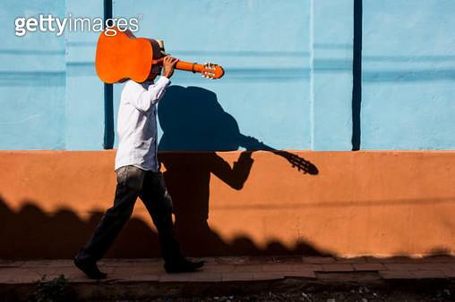 Cuba, man with guitar walking on the street - gettyimageskorea