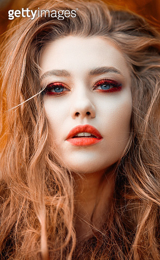 Beautiful blond young woman with blue eyes and red-pink makeup and red lips looking at the makeup, fire and sensual concept - gettyimageskorea