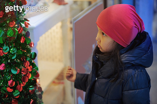Cute girl looking to the srore showcase with Christmas tree decorated - gettyimageskorea