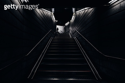 Man walking into the light in the dark tunnel from underground - gettyimageskorea