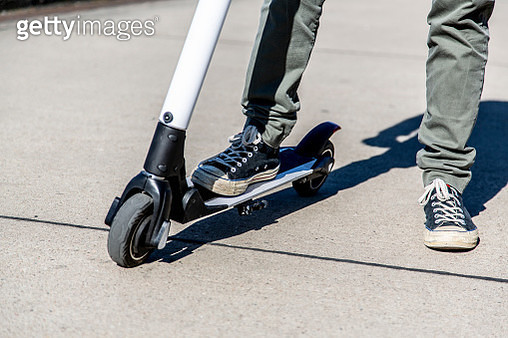 Man standing on E-Scooter - gettyimageskorea