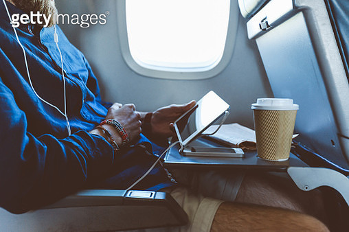 Man using digital tablet in airplane - gettyimageskorea