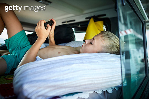 Boy with cell phone lying in off-road vehicle - gettyimageskorea