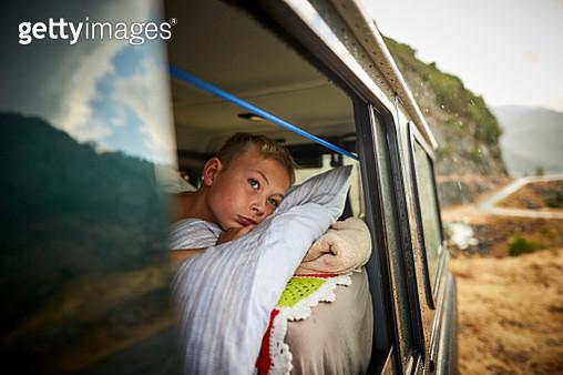 Boy lying on mattress in off-road vehicle - gettyimageskorea