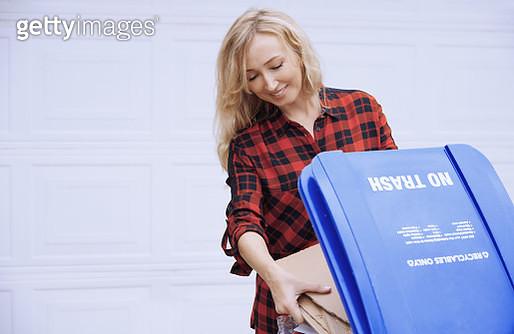Woman putting paper garbage to the recylcing bin - gettyimageskorea