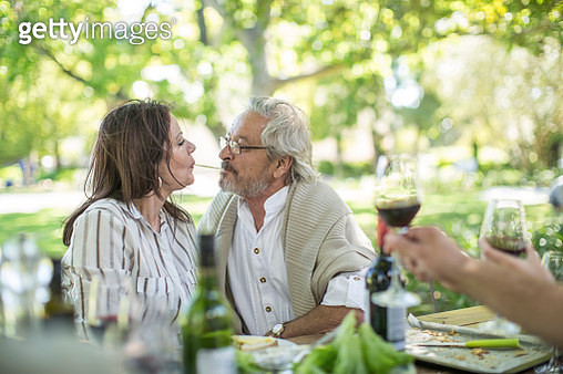 Senior couple sharing spaghetti at outdoor table - gettyimageskorea