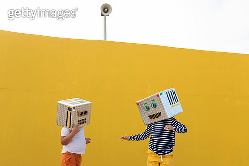 Friends wearing robot costumes standing against yellow wall - gettyimageskorea