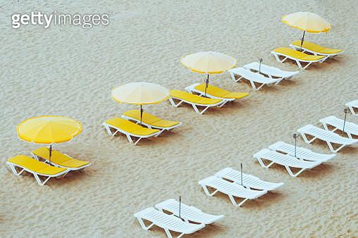 Beach umbrellas and loungers on an empty beach - gettyimageskorea