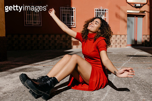 Young woman wearing red dress and sitting on ground - gettyimageskorea
