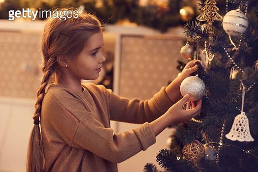 Cute girl hanging Christmas bauble on tree - gettyimageskorea