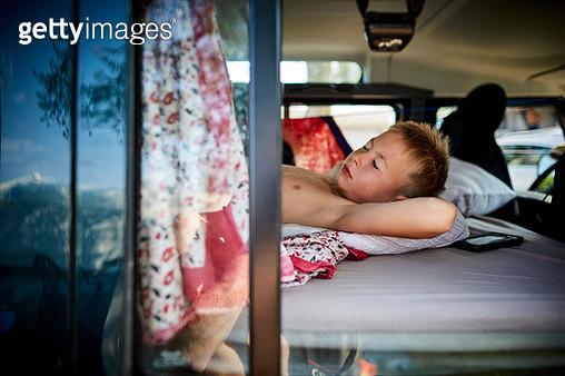 Boy sleeping on mattress in off-road vehicle - gettyimageskorea