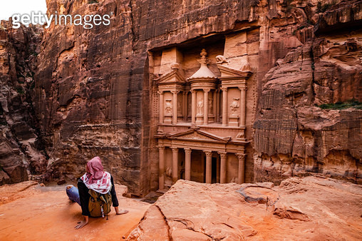 Tourist contemplating The Al-Khazneh Treasury tomb in the city of Petra from viewpoint. - gettyimageskorea