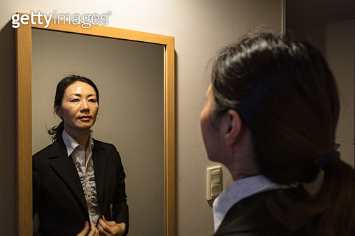 Female businessperson looking at the mirror in a dark room - gettyimageskorea