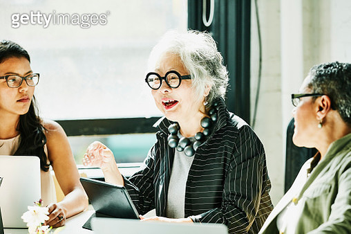 Senior businesswoman leading team meeting in office conference room - gettyimageskorea