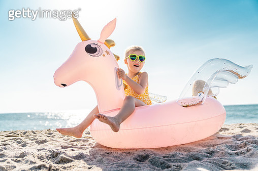 Beach scene - five years old little girl, wearing swimsuit and sunglasses, sitting on a giant pink inflatable unicorn. Sea and clear blue sky on the background. - gettyimageskorea