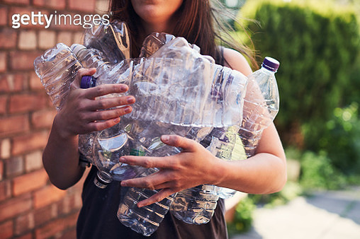 Young woman recycling plastic bottles - gettyimageskorea