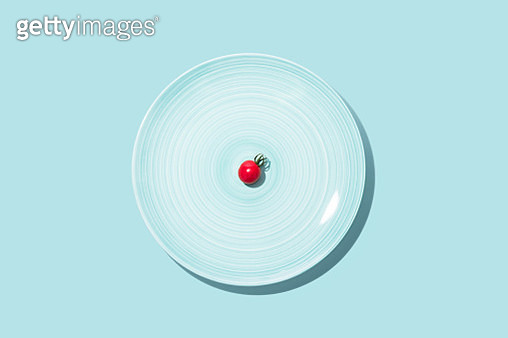 Small Cherry Tomato With Big Blue Plate on Solid Blue Background Directly Above View.Diet Concept, Focus Concept. - gettyimageskorea