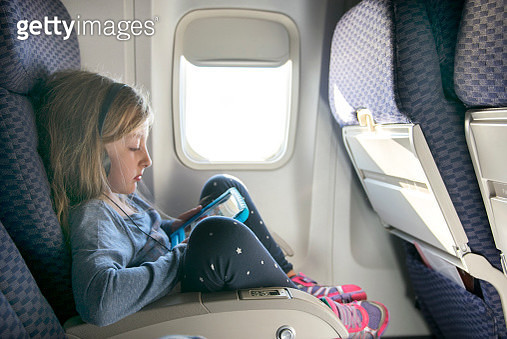 Girl watching a movie on a tablet in an airplane - gettyimageskorea