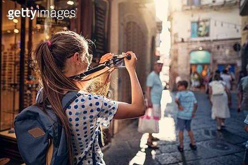 Family sightseeing Italian town in Campania. Teenage girl is walking a narrow street and taking photos. Nikon D850 - gettyimageskorea