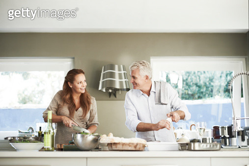 Mature couple looking at each other while preparing food together at counter in kitchen - gettyimageskorea