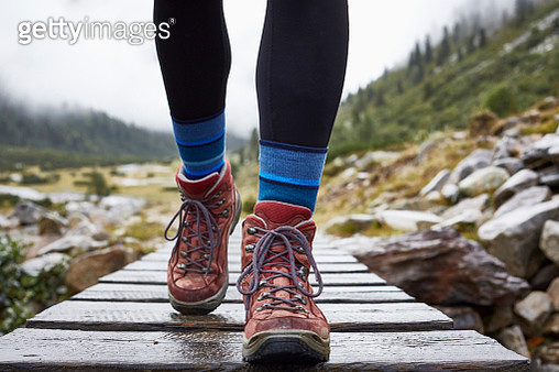 Female hiker hiking across wooden footbridge, cropped view of legs and hiking boots - gettyimageskorea