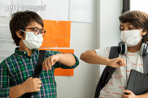 Boys wearing masks giving elbow bump while standing against wall in school - gettyimageskorea