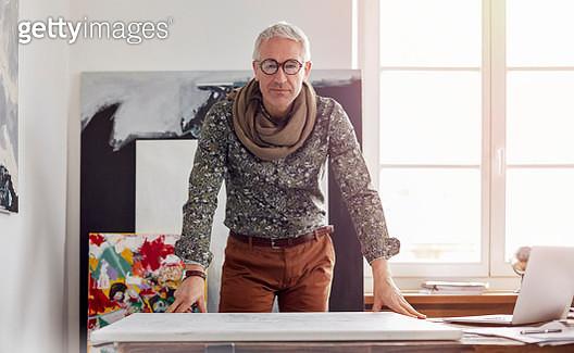 Portrait confident male photographer standing over canvas in art studio - gettyimageskorea