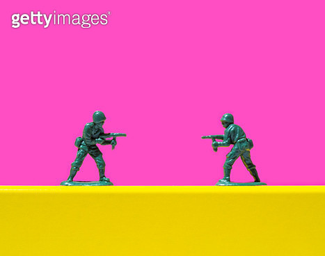 Two toy soldiers pointing guns at each other - gettyimageskorea