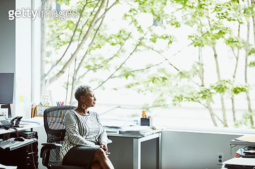 Businesswoman looking out window while sitting at office workstation - gettyimageskorea