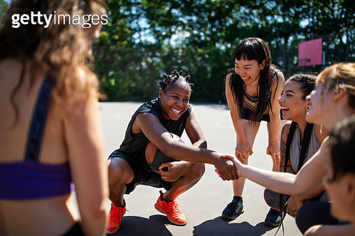 Female basketball player shaking hands during a game plan on court. Multi-ethnic basketball team on outdoor court. - gettyimageskorea