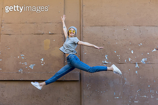 Young woman jumping front of wall - gettyimageskorea
