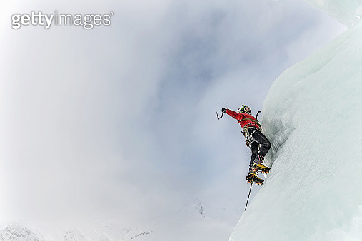Male mountain climber ascending a wall of ice in the Austrian Alps - gettyimageskorea