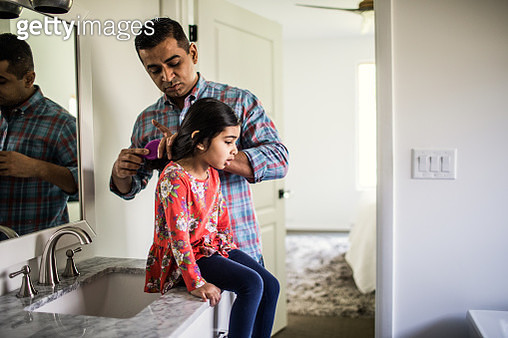 Father brushing daughters hair in bathroom - gettyimageskorea
