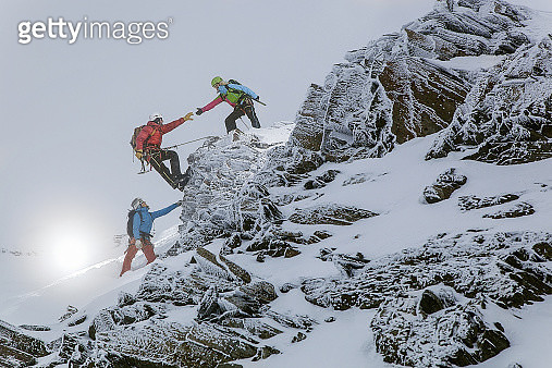 A group of mountain climbers navigate a rocky ledge  in the Austrian Alps - gettyimageskorea