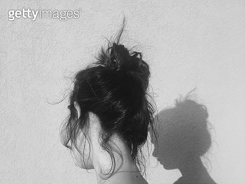 Rear View Of Woman With Hair Bun Standing Against Wall - gettyimageskorea