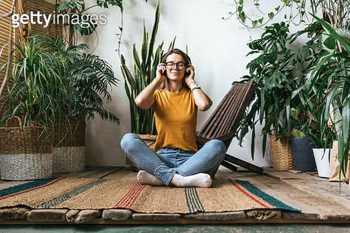 Relaxed young woman sitting on the floor at home listening to music - gettyimageskorea