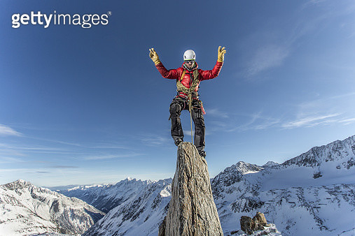 Male mountain climber on top of a stone on a peak in the Austrian Alps - gettyimageskorea