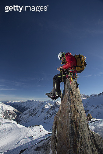 Male mountain climber sitting on a stone writing an sms on a peak in the Austrian Alps - gettyimageskorea