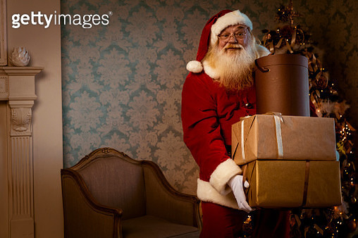 Santa Claus carrying gifts - gettyimageskorea