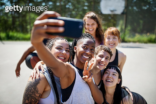 Multiracial basketball team taking selfie on court - gettyimageskorea