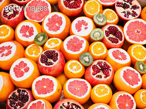 Fresh oranges, grapefruit, pomegranate and kiwi fruit with ends sliced arranged neatly to form a vibrant pattern - gettyimageskorea