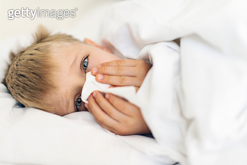 Sick little boy cleaning nose in bed - gettyimageskorea
