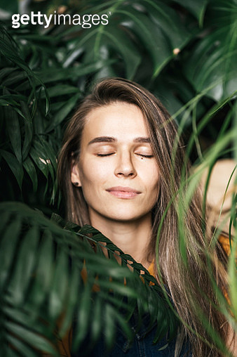 Portrait of a young woman with closed eyes amidst green plants - gettyimageskorea