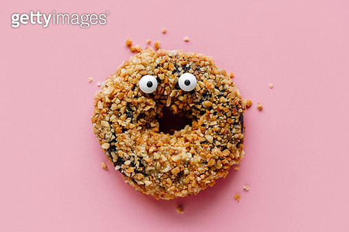 Close-Up Of Donut With Anthropomorphic Face Over Pink Background - gettyimageskorea