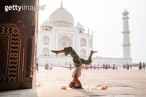 Young woman practicing yoga in India at the famous Taj Mahal at sunrise - Headstand position upside down- People travel spirituality zen like concept - gettyimageskorea