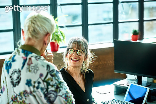 Cheerful mature woman at desk smiling towards senior female colleague - gettyimageskorea