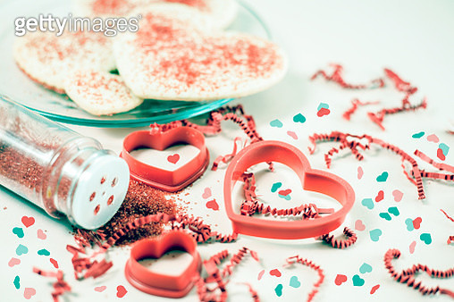 Valentine's Day cookies and pastry cutters with red sprinkles. - gettyimageskorea