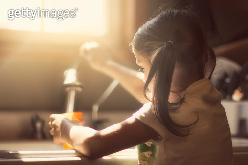 Girl filling cup with water from kitchen faucet - gettyimageskorea