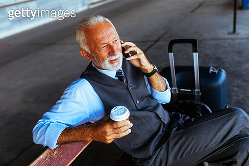 Senior businessman using mobile device while waiting for his train - gettyimageskorea
